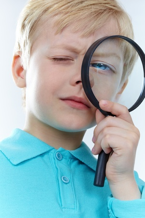 Portrait of a kid looking through magnifying glass photo