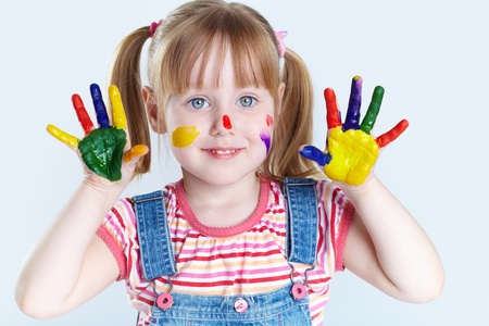 kids painted hands: Girl having fun, her face and palms being covered with paint