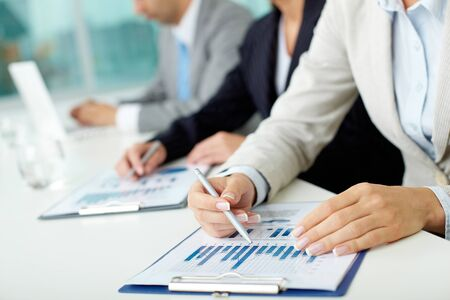 summary: Business people sitting at the table and analyzing graphs