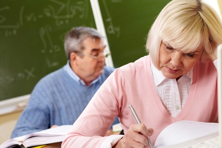 cope: Pensive seniors trying to cope with a hard task in school, tilt up Stock Photo