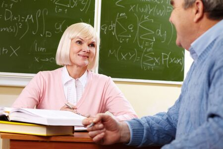 congenial: Elderly people looking at each other with a smile during the break between lessons Stock Photo
