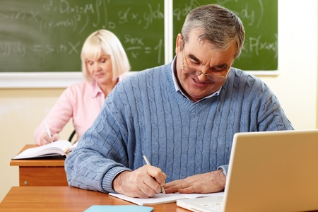 Senior man with a cheerful smile doing the task in classroom photo