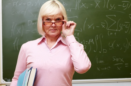 strict: Portrait of an elegant senior lady standing near the blackboard and looking strictly at camera