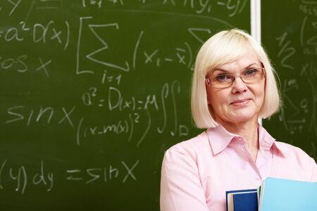 director de escuela: Encantadora mujer mayor que presenta con una sonrisa delante de la cámara