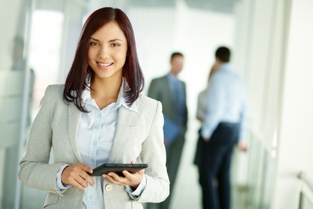 Business woman standing in foreground with a tablet in her hands, her co-workers discussing business matters in the background, tilt up photo