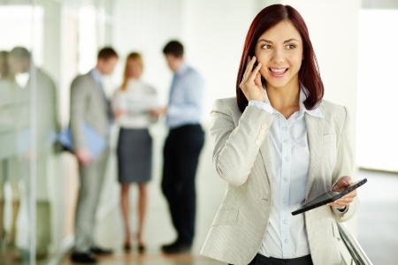 on the phone business: Business lady answering the phone with a smile, receiving good news Stock Photo