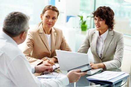 Business-Frauen aufmerksam zuhören, um ihre älteren erfahrenen Kollegen
