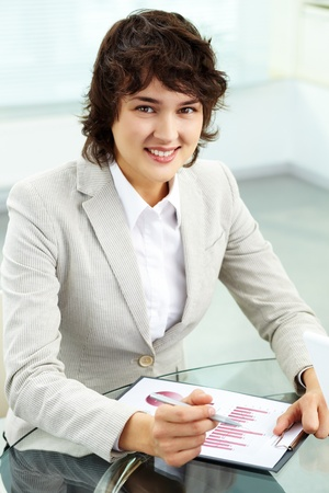 Vertical portrait of a business woman analyzing graphs and looking at camera with a smile photo