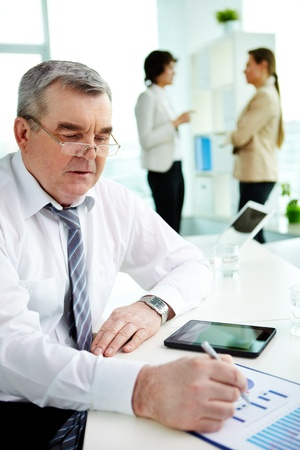 Mature businessman checking the business data presented in graphs photo