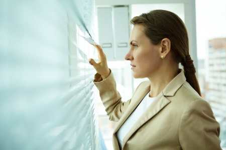 Pleasant midage business woman looking outside through jalousie