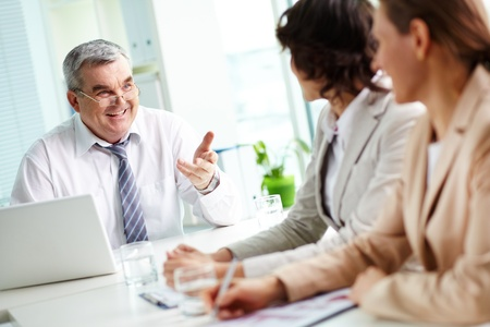 Mature leader approving his colleagues� fresh ideas, tilt up photo