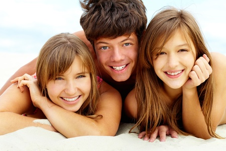 Three tanned young people lying on sand and looking at camera with toothy smiles photo