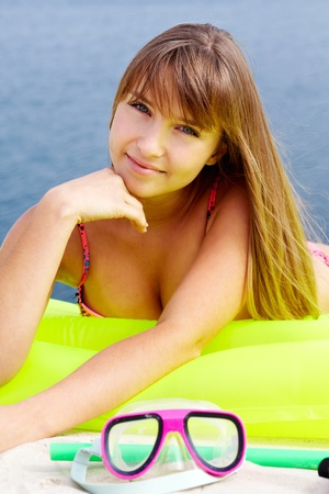 lilo: Pretty teenage girl lying on an air bed and looking at camera with a smile Stock Photo