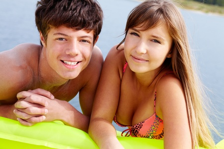 lilo: Cheerful teen boy and girl lying together on a lilo, tilt up