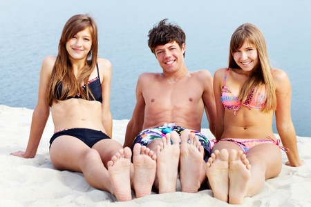 Young people sitting on sand and tanning on a sunny summer day photo