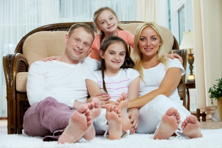 girl soles: Portrait of happy family with two children sitting at home
