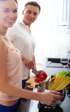 Portrait of amorous couple cooking spaghetti and salad in the kitchen Stock Photo - 13119187