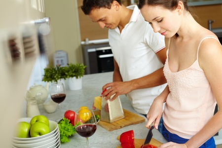 woman cooking: Portrait of husband and wife cooking together in the kitchen  Stock Photo