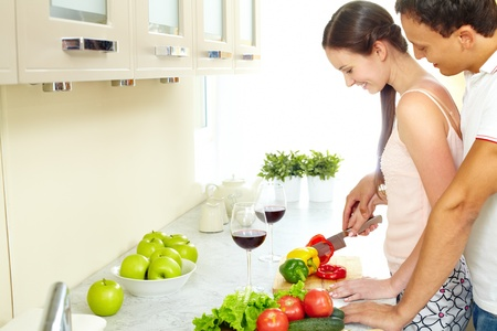 Portrait of pretty female cooking salad with her husband near by  photo