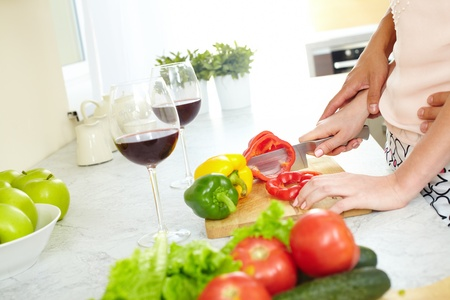 Close-up of young female cutting red pepper in the kitchen  photo