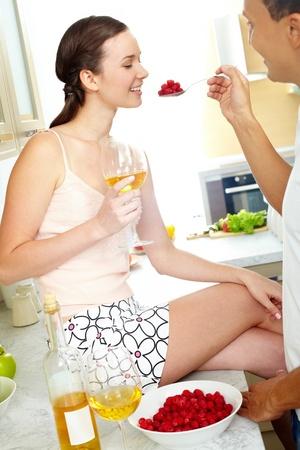 cuiller�e: Image d'une femme heureuse avec un verre de vin regardant cuiller�e de framboises � la main mari