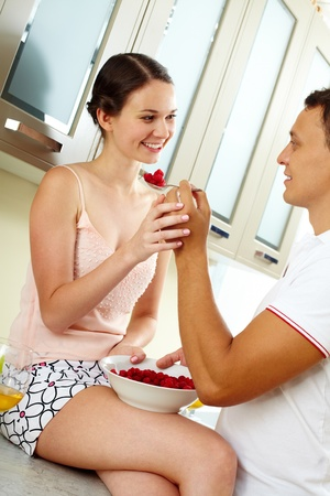 Image of happy woman looking at her husband with spoonful of raspberries photo