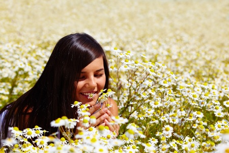 among: Attractive brunette lying among flowers and smiling
