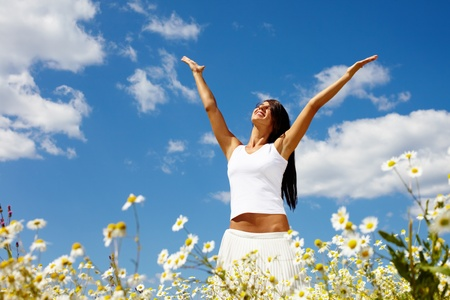 Young woman holding hands high up enjoying the warm sunny day Stock Photo - 13119352