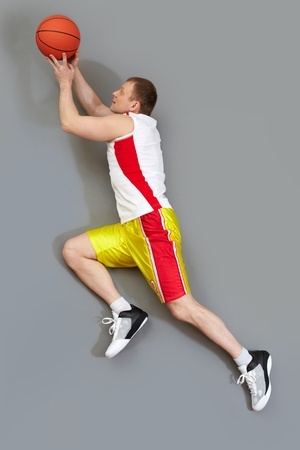 Muscular basketball player slamming the ball, overview photo