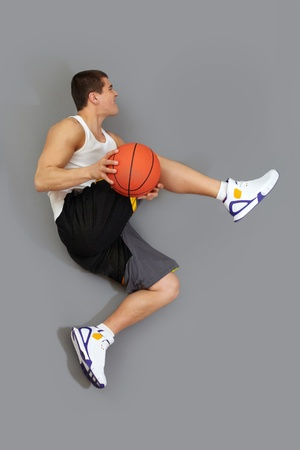 dunk: Basketball player executing a tricky jump with a ball Stock Photo