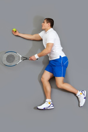Handsome guy playing tennis serving the ball photo