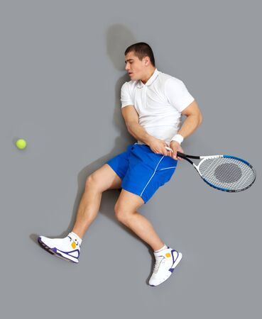 Energetic guy with a tennis racket playing the ball photo