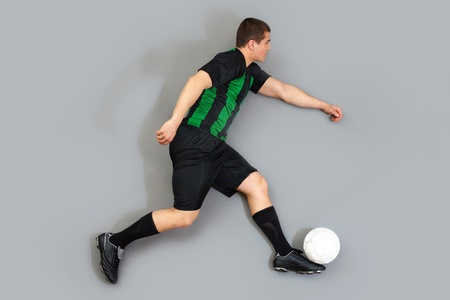 Man in uniform dribbling the ball, isolated on grey background photo