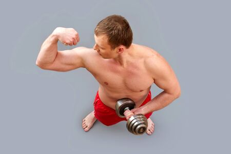 Guy proudly flexing his muscle, the above view, isolated on grey photo