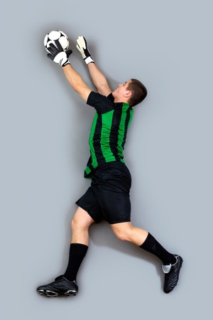 Portrait of a goalkeeper in movement catching the ball photo