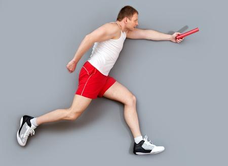 Sportive guy hurrying to pass the relay baton photo