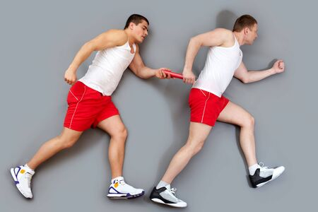 Two guys taking part in a relay race passing the baton photo