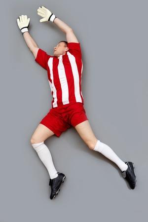 골키퍼: 골키퍼는 공을 잡으려고 높은 점프 스톡 사진