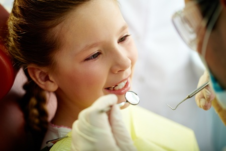 a dentist: Close up portrait of a little smiling girl at dentist�s office