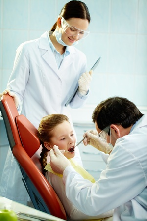 usual: Young patient undergoing usual check-up procedure at dentist�s Stock Photo