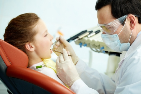 Side view of a dentist and his patient photo