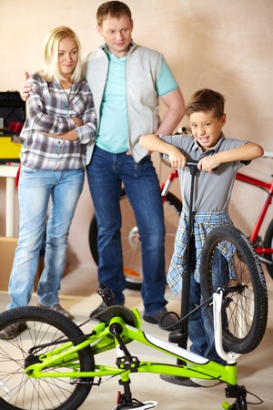 Portrait of cute boy pumping bicycle wheel with his parents on background Stock Photo - 13119205