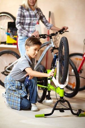 Portrait of cute boy repairing bicycle wheel with his mother on background photo