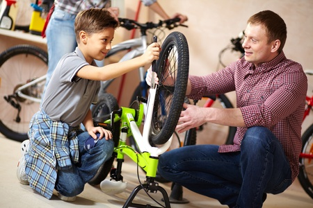 Portrait of cute boy repairing bicycle wheel with his father helping him near by photo