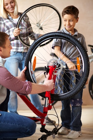 bicyclists: Portrait of cute boy holding bicycle wheel with his father near by