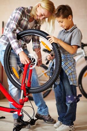 racing bike: Portrait of cute boy and his mother repairing bicycle