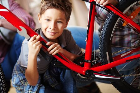 Portrait of cute boy with bicycle looking at camera Stock Photo - 13119163