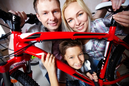Portrait of happy family with bicycle looking at camera photo