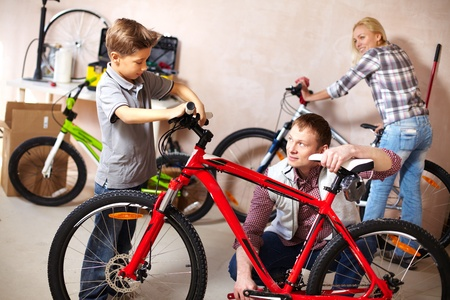 Portrait of cute boy and his father repairing bicycle in garage photo