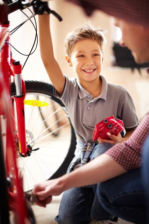 mountainbike: Portrait of cute boy looking at his father repairing bicycle in garage Stock Photo